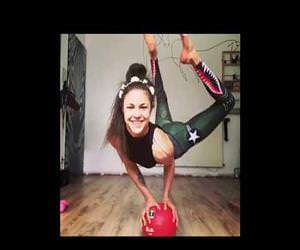 A girl puts glasses on with legs while standing on a ball with hands Funny Video